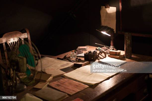 high angle view of books with desk lamp on table in darkroom - angle poise lamp stock pictures, royalty-free photos & images
