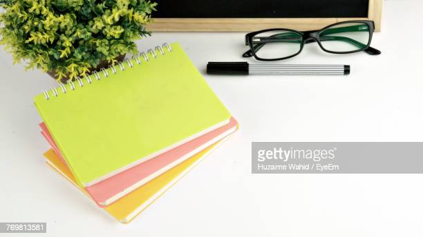 High Angle View Of Books With Eyeglasses And Pen On Table