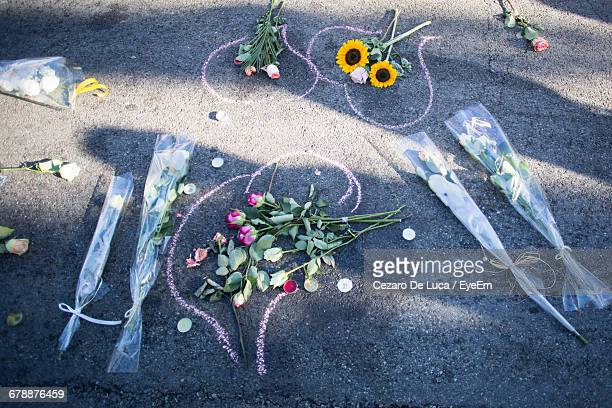high angle view of bouquets and tea lights on chalk drawing at road after terrorist attack - memorial event stock pictures, royalty-free photos & images