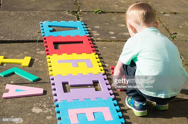 High Angle View Of Boy Arranging Alphabets On Street