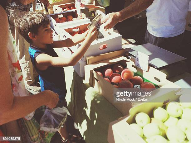 High Angle View Of Boy Buying Fruit With Mother In Market