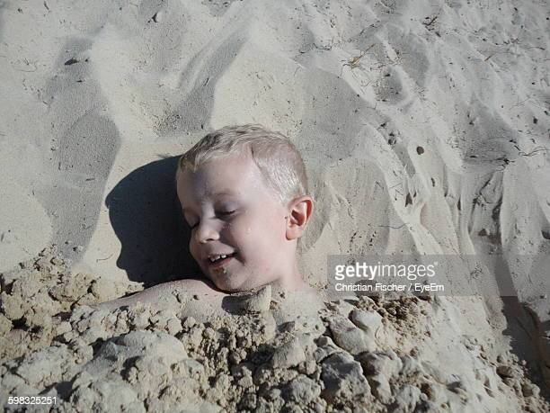 High Angle View Of Boy Covered With Sand At Beach