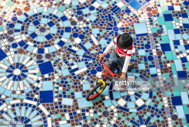 high angle view of boy cycling on mosaic walkway - mosaik stock-fotos und bilder
