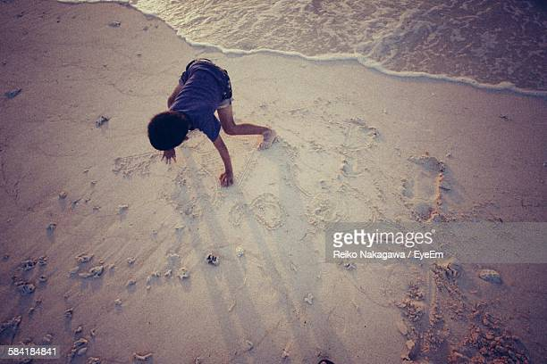 High Angle View Of Boy Drawing On Sand At Beach