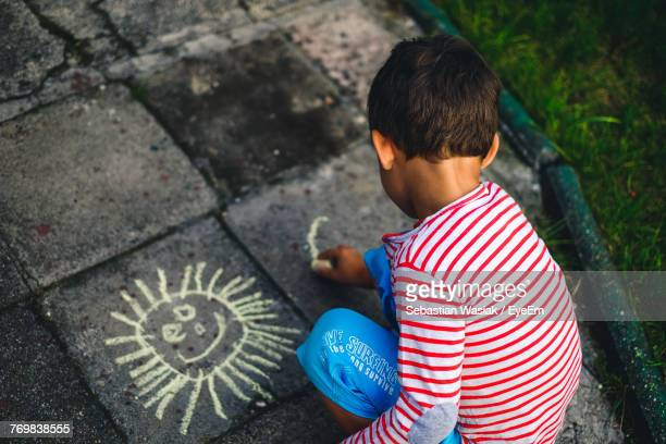 High Angle View Of Boy Drawing With Chalk Outdoors