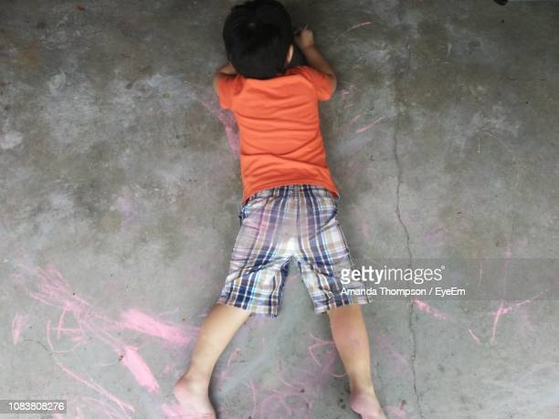 High Angle View Of Boy Drawing With Chalk While Lying On Footpath
