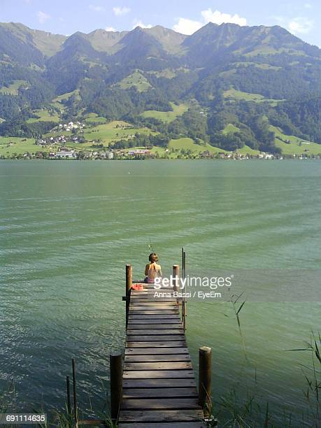 high angle view of boy fishing while sitting on jetty over lake against mountain - anna fischer stock-fotos und bilder
