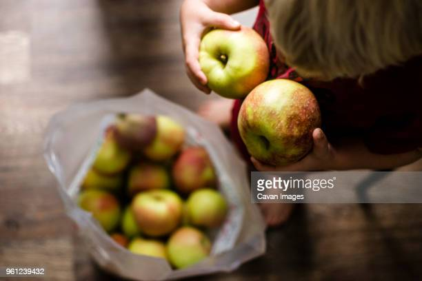 High angle view of boy holding apples while standing at home