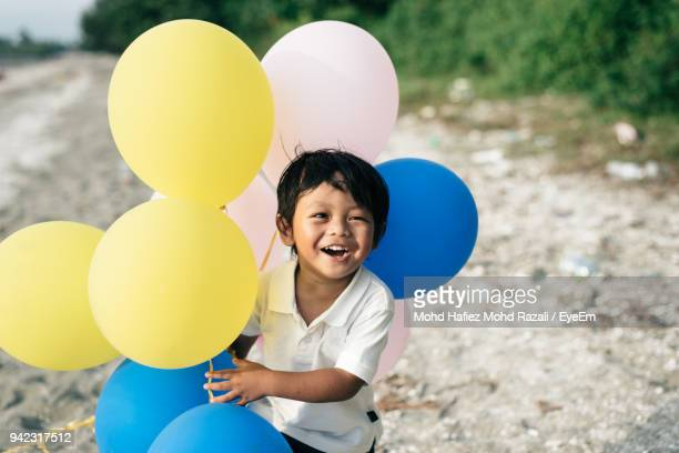 High Angle View Of Boy Holding Balloon While Standing On Ground