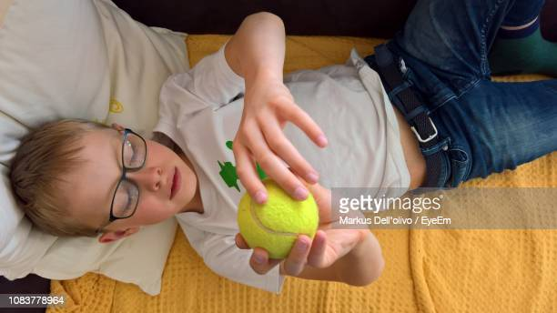 High Angle View Of Boy Holding Tennis Ball While Lying On Bed At Home