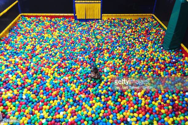 High Angle View Of Boy In Multi Colored Ball Pool
