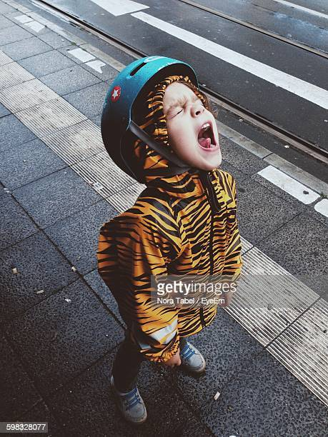 high angle view of boy in tiger print raincoat shouting on sidewalk - shouting stock photos and pictures