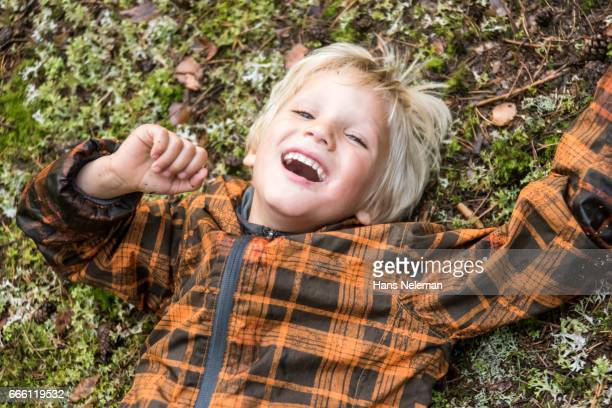 high angle view of boy laughing while lying on grass - hans neleman ストックフォトと画像