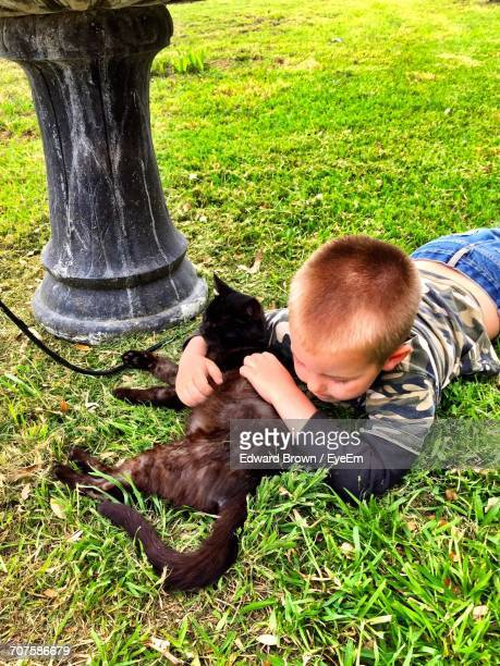 high angle view of boy lying down with cat on grassy field - lying on front stock pictures, royalty-free photos & images