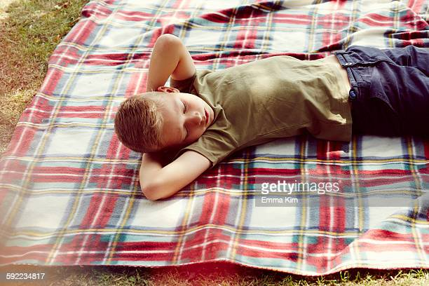 High angle view of boy lying on picnic blanket hands behind head looking away