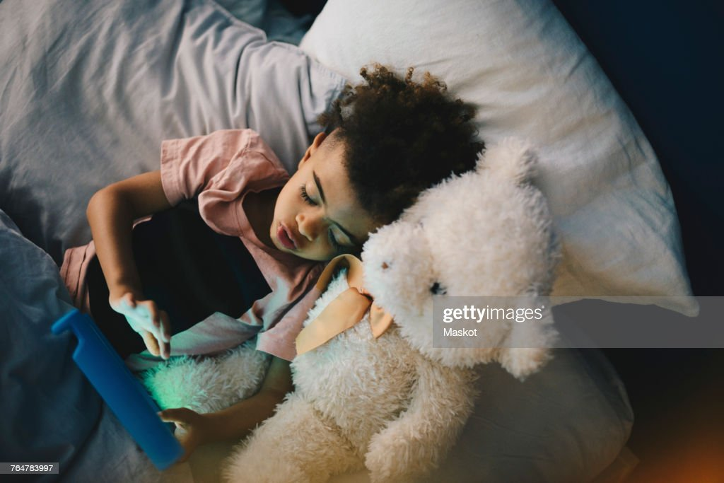 High angle view of boy lying with teddy bear while using digital tablet on bed at home : Stock Photo