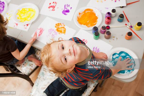 High angle view of boy (4-5) making palm print