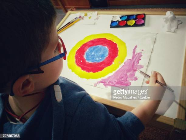 High Angle View Of Boy Painting On Paper At Home