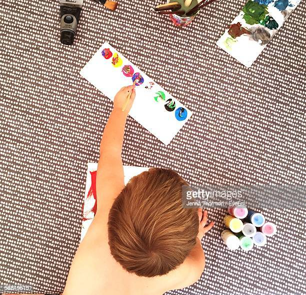 High Angle View Of Boy Painting Picture At Home