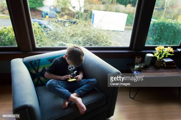 High angle view of boy playing game on mobile phone while sitting on armchair