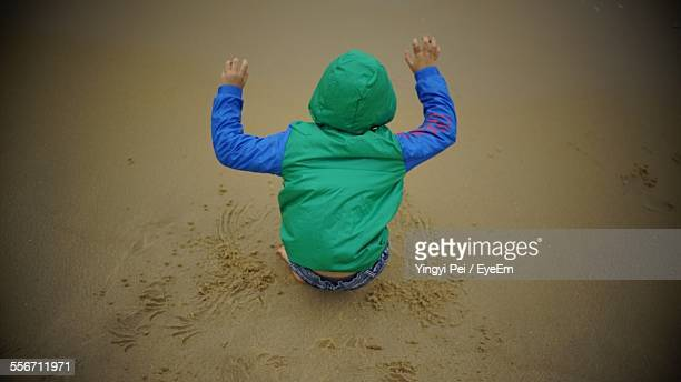 High Angle View Of Boy Playing On Sandy Beach