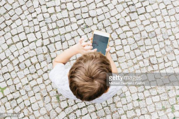 High Angle View Of Boy Playing On Smart Phone
