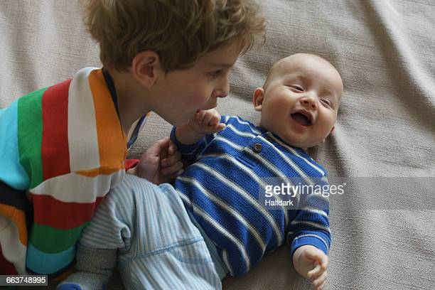 High angle view of boy playing with toddler on bed at home