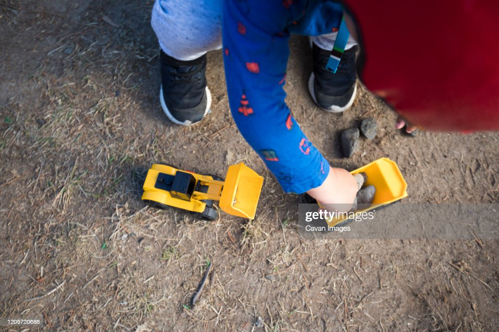 High angle view of boy playing with toy construction vehicles. : Stock Photo