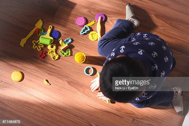 High Angle View Of Boy Playing With Toys At Home