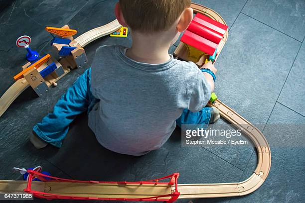 High Angle View Of Boy Playing With Train Set On Floor At Home
