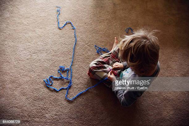 High Angle View Of Boy Playing With Woolen Thread At Home