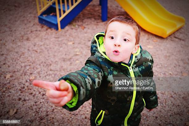 High Angle View Of Boy Pointing Towards Something At Playground