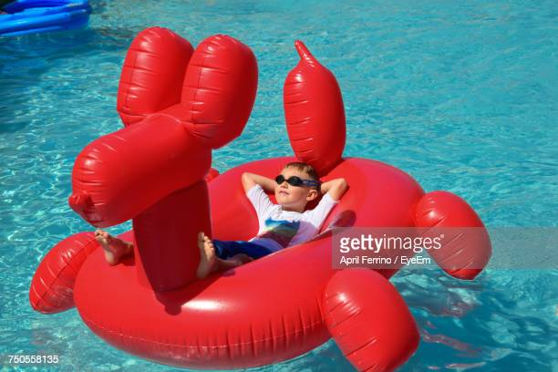 high angle view of boy relaxing on inflatable ring in swimming pool during sunny day - red tube stock pictures, royalty-free photos & images