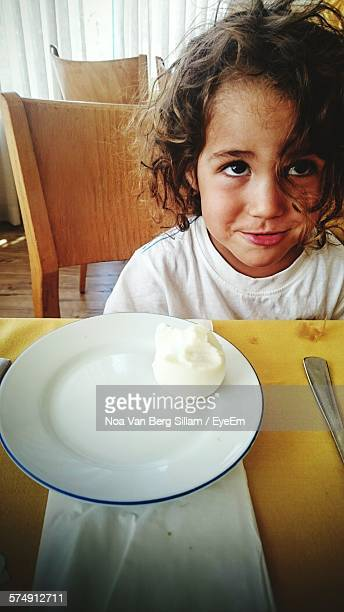 High Angle View Of Boy Sitting On Dinning Table
