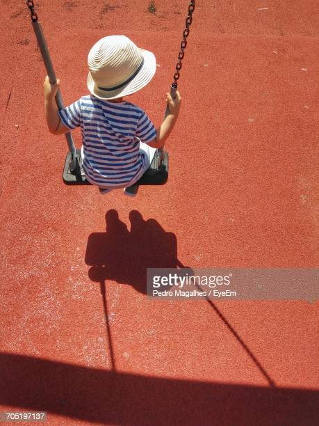 High Angle View Of Boy Sitting On Swing