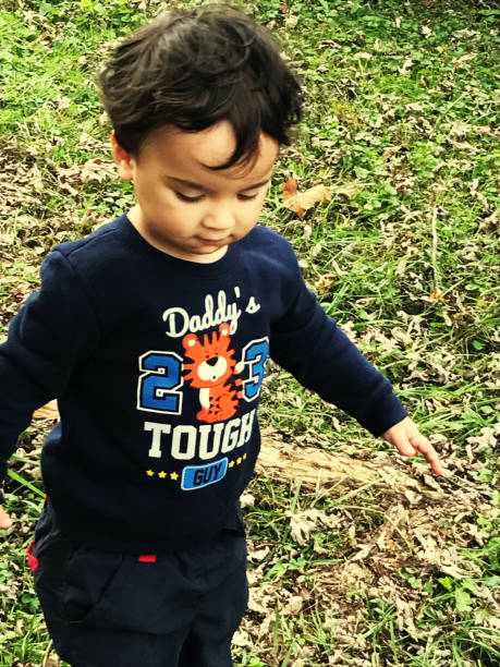 High Angle View Of Boy Standing On Grass Outdoors