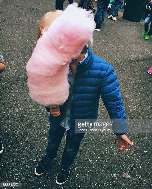 High Angle View Of Boy Standing With Cotton Candy On Street