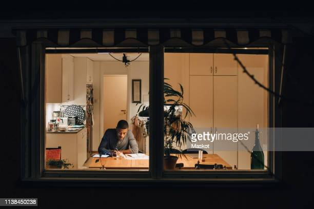 high angle view of boy studying while sitting at home seen through window - window stock pictures, royalty-free photos & images