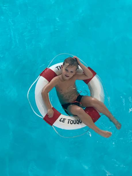 High Angle View Of Boy Swimming In Pool With Lifebuoy