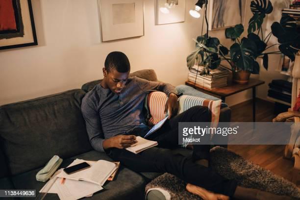 high angle view of boy using digital tablet while studying on sofa at home - matemática opção educacional - fotografias e filmes do acervo