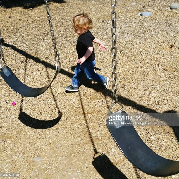 High Angle View Of Boy Walking By Swing At Playground