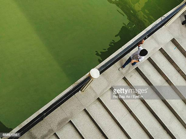 High Angle View Of Boy Walking On Footbridge