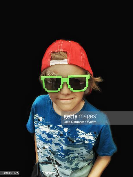 High Angle View Of Boy Wearing Big Green Sunglasses Against Black Background