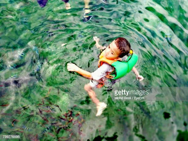 High Angle View Of Boy Wearing Life Jacket While Swimming In Lake