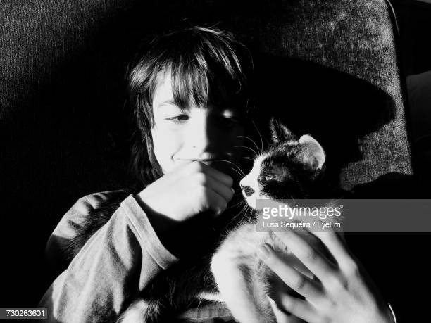 High Angle View Of Boy With Cat Resting On Bed At Home