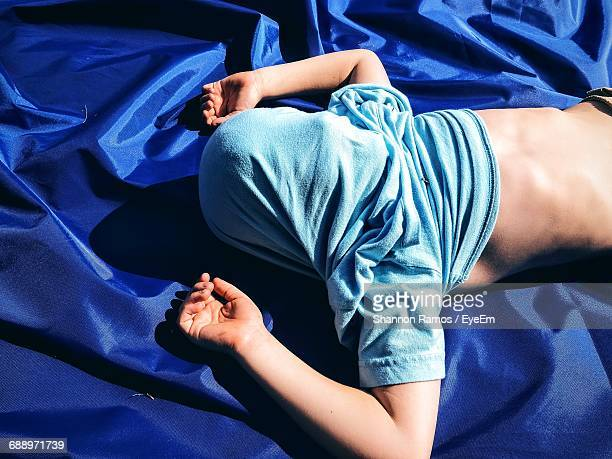 High Angle View Of Boy With Covered Face Sleeping On Blue Fabric In Yard