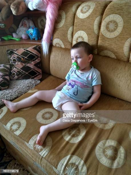 high angle view of boy with pacifier in mouth sitting on sofa at home - diaper boy stock photos and pictures
