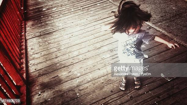 High Angle View Of Boy With Tousled Hair On Boardwalk