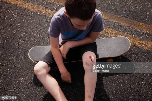 high angle view of boy with wounded knee sitting on skateboard - down on one knee stock pictures, royalty-free photos & images