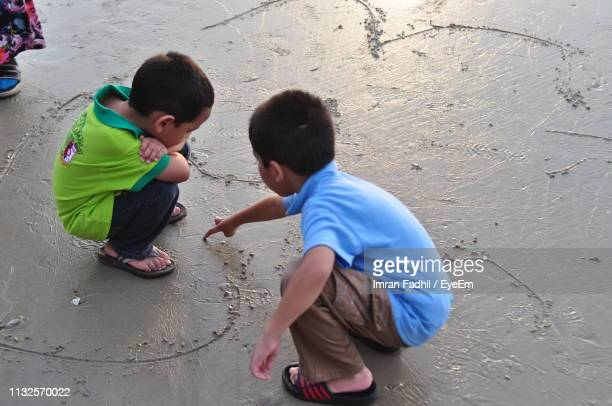 high angle view of boys playing on shore at beach - 背景に人 ストックフォトと画像